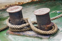 Old mooring bollard with heavy ropes, closeup.