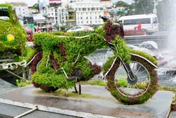 Old motorbike decorated with flowers on a roundabout in Da Lat, Vietnam