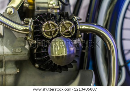 Old motorcycle engine with polished caps steel polished pipes parts and matte block, close up #1213405807
