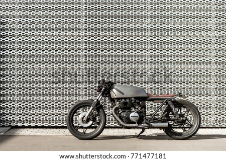 Old motorcycle parking near wall of industrial building. Everything is ready for having fun driving the empty road on a motorcycle tour journey. Modern man hobby. Space for your individual text.