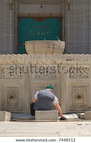 Old muslim man preparing for the prayer in the courtyard of a mosque