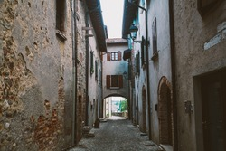 old narrow alley in tuscan village - antique italian lane in Montalcino, Tuscany, Italy.