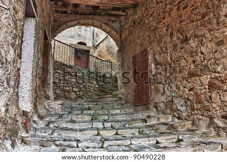 old narrow alley with staircase and vault in tuscan town - antique italian lane in Tuscany, Italy