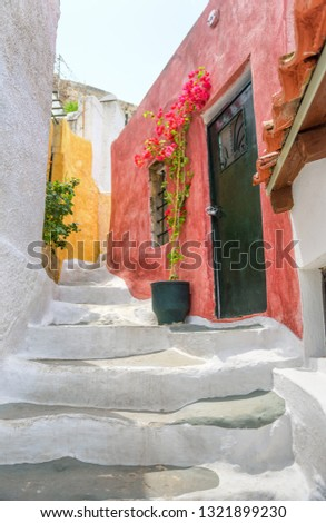 Old narrow street in Anafiotika, Plaka district, Athens, Greece. Plaka is a famous tourist attraction of Athens. Beautiful cozy alley between white houses on the Acropolis slope in the Athens center.