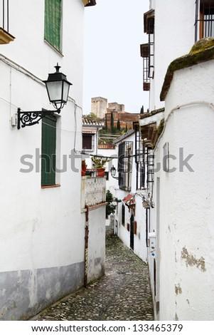 Old narrow street in Granada, Spain - stock photo