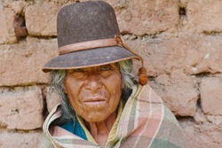Old native american woman wearing typical aymara clothes. Adobe wall background.