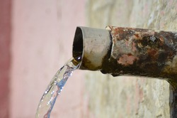 Old natural flowing fountain tap from stone wall of village fountain - wasted water