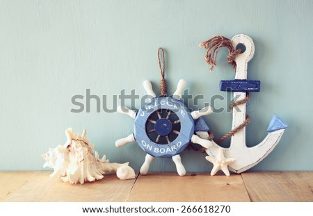 old nautical wood wheel, anchor and shells on wooden table over wooden background. vintage filtered image