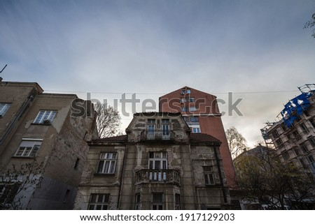 Old, neglected and decaying residential housing building surrounded by modern towers, some under construction, in a developping area of Belgrade, Serbia.   Stock photo ©