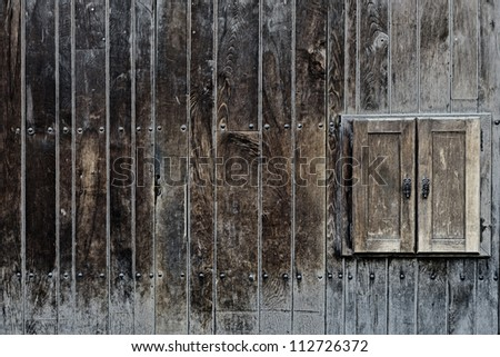 Old neglected rustic shutters closed on aging wooden wall