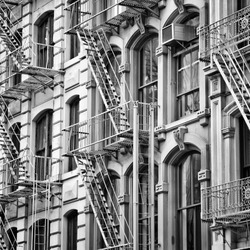 Old New York City architecture. Fire escape stairs. Black and white style.