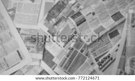 Old newspapers scattered on the floor. Lots of retro journals with headlines, articles and photos. Background texture, blurred, top view #772124671