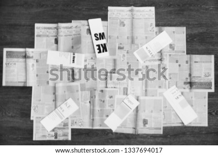 Old newspapers scattered on wooden floor. Lots of retro journals with headlines, articles and photos. Background texture, blurred, top view                 #1337694017