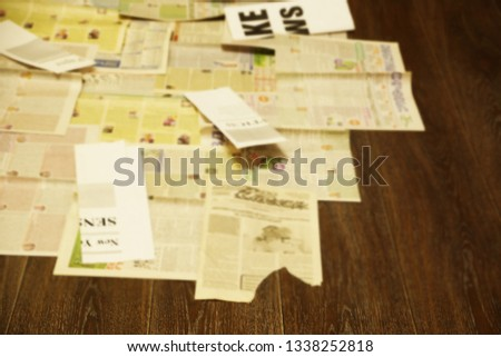Old newspapers scattered on wooden floor. Lots of retro journals with headlines, articles and photos. Background texture, blurred, side view                            #1338252818