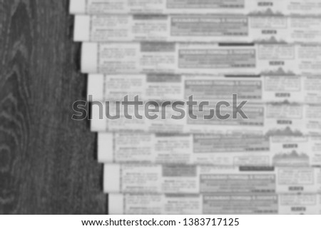 Old newspapers scattered on wooden floor. Lots of retro journals with headlines, articles and photos. Background texture, blurred, top view