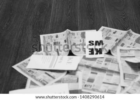 Old newspapers scattered on wooden floor. Lots of retro journals with headlines, articles and photos. Background texture, blurred, side view