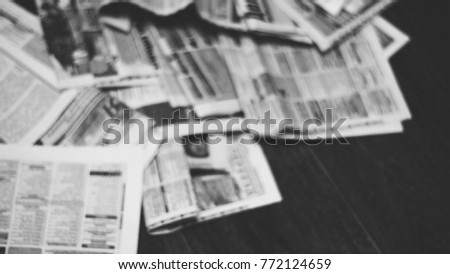 Old newspapers scattered on wooden floor. Lots of retro journals with headlines, articles and photos. Background texture, blurred, side view #772124659