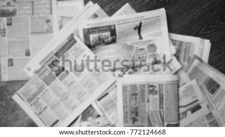 Old newspapers scattered on wooden floor. Lots of retro journals with headlines, articles and photos. Background texture, blurred, top view #772124668