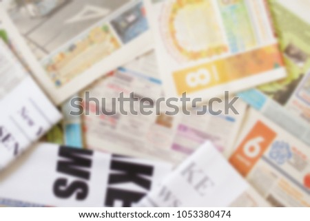 Old newspapers with headlines and articles, blurred background  #1053380474