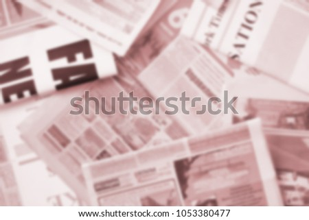 Old newspapers with headlines and articles, blurred background  #1053380477
