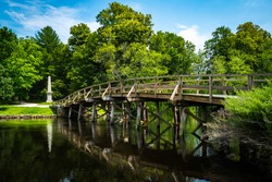 Old North Bridge at Minute Man National Historical Park in Concord, Massachusetts. Tranquil Nature Landscape with Landmark Bridge and Clean River. Peaceful American New England Image.