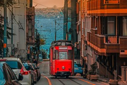 Old nostalgic tram going through the streets of Kadikoy district on the Asian side of Istanbul. The trendy neighborhood is full of colorful buildings. Marmara Sea.