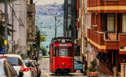 Old nostalgic tram going through the streets of Kadikoy on the Asian side of Istanbul. The trendy neighborhood is full of colorfull buildings. And Marmara Sea