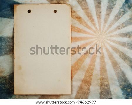 Old notepad sheet on sunburst grunge retro background