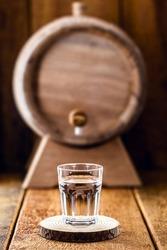 Old oak barrel and glass of high quality distilled alcohol. Brazilian silver cachaça, called pinga, vodka, white rum, liqueur, pure drink, Poitín, sake, brandy or Absinthe.