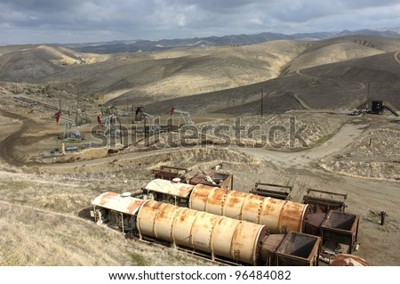 Old oil field heaters are in the foreground while downhill a group of oil wells are located in the foothills of the Sierra Nevada, California