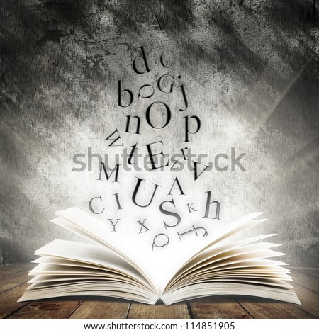 Old open book with magic light and falling letters on wood planks and dark abstract background