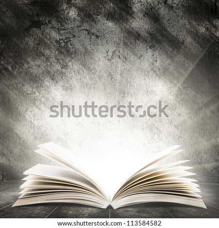 Old open book with magic light on a dark abstract background