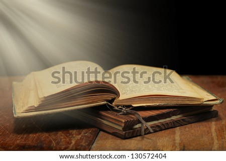 Old open book with magic light on wooden table