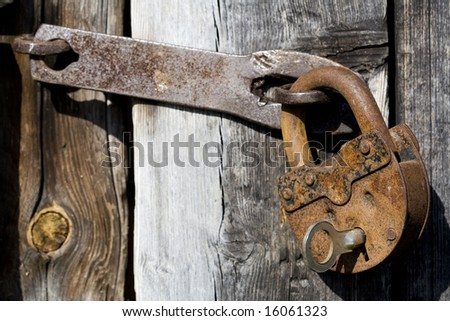 Old opened rusty and dirty metal lock with key on a old wood door