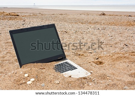 old or obsolete unwanted laptop on the beach with blank screen for your own message good concept for unwanted technology or travel websites