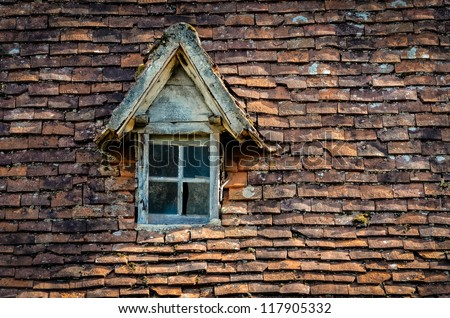 Old orange brick roof with broken glass retro winow