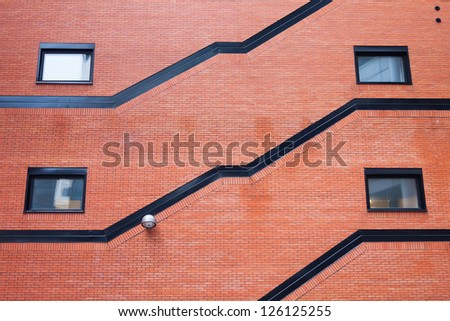 Old orange brick wall with four windows and street lamp