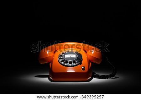 old orange retro phone on black background #349395257