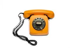 Old, orange rotary dial telephone, isolated on white background.