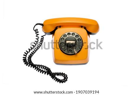 Old, orange rotary dial telephone, isolated on white background. Stockfoto ©
