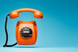 Old orange telephone rings with handset off.