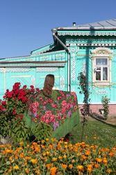 Old ornamental windows, carved frames. Vintage wooden rural house in Suzdal town, Russia. Decorative red climber roses, bush: season flowers in summer garden. Russian girl in folk Pavlovo Posad shawl