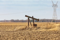 Old, orphaned oil well pump in farm field.  oil well abandonment, decommission, and oil production concept.