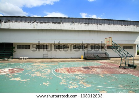 Old outdoor basketball court against blue sky