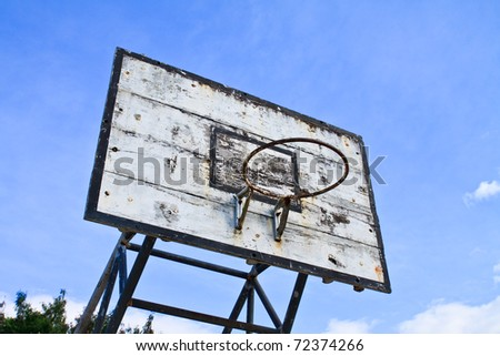 old outdoor basketball hoop against blue sky background - stock photo