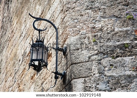 Old outdoor street lamp on stone wall near the palace in Monaco.