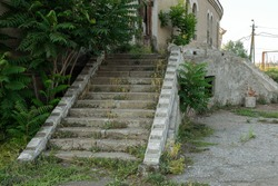 Old overgrown with destroyed stone balustrades old antique steps of a stone staircase. Ruined stairs. The dilapidated building, the destroyed stone steps of the stairs. Ancient stone staircase