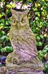 Old owl stone sculpture in a garden.