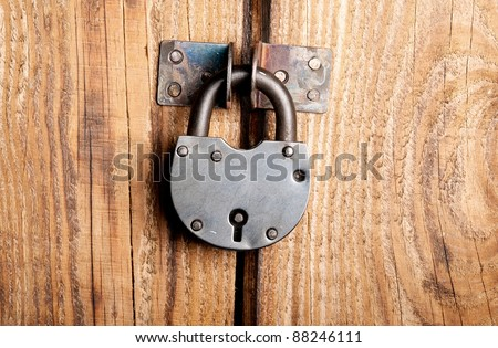 Old padlock on a wooden door #88246111