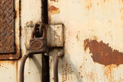 Old padlock on rusty iron door. Old rusty key lock steel door. Old locked door.